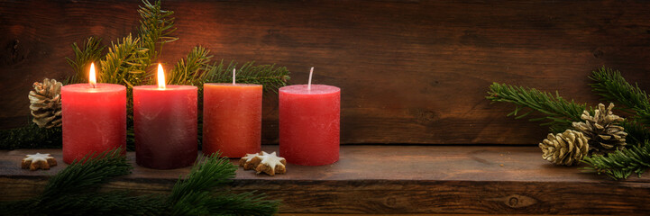 Second Sunday in Advent, four red candles, two of them are burning, fir branches and Christmas decoration on dark rustic wood, wide panoramic format with copy space