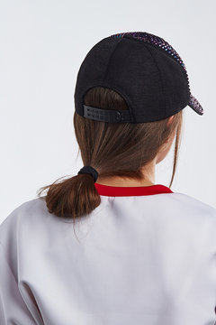 Medium close-up back shot of girl in a white top with red collar and a black baseball cap with purple rhinestone studding and a plastic snap closure. The girl's brown hair are fastened in casual bun.