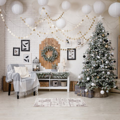 Modern black and white interior design room with Christmas and New Year decorations, toys, gifts, snow-covered fir tree, garlands. Winter holidays composition.