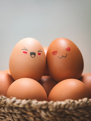 Egg lovers have happy faces of men and women on the pile of eggs in the basket with copy space. Organic egg food ingredients, Couples, Easter, Valentine's day concept.