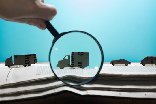 Magnifying glass in front of an open newspaper with paper cars. Concept of car rent, search, purchase and cargo transportation.