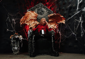 passionate lazy Cupid blond long hair guy in red leather jacket and vinyl pants with huge Golden wings sits on a huge throne in hell