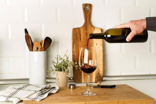 Mano con una botella de vino tinto sirviendo una copa de vino en la cocina. Vista de frente