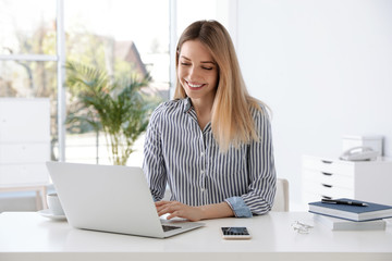 Young businesswoman using laptop at table in office