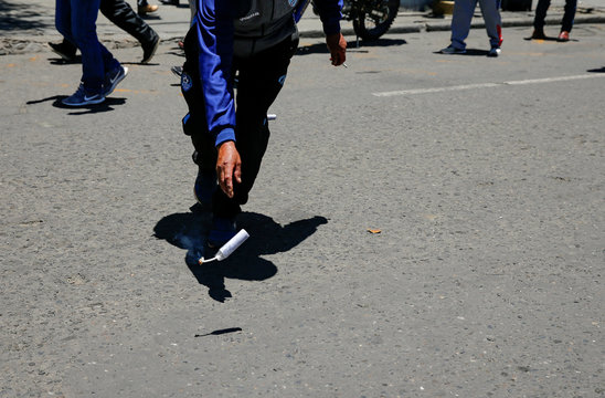 A miner throws a dynamite stick as he takes part in a march to support Bolivia's President Evo Morales in La Paz