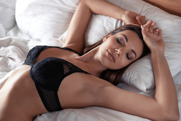Obraz Sexy young woman in black lingerie lying on bed - fototapety do salonu