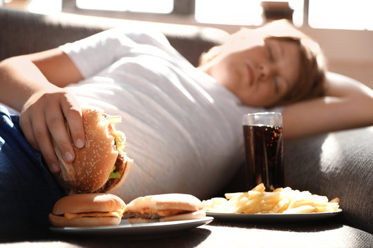 Overweight boy sleeping on sofa surrounded by fast food