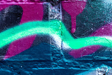 Fragment of colored graffiti painted on a brick wall.