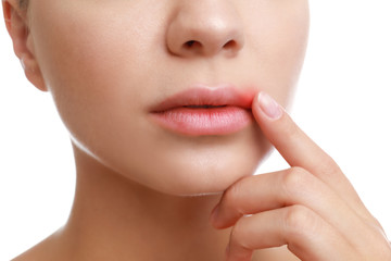 Young woman with cold sore touching lips against white background, closeup