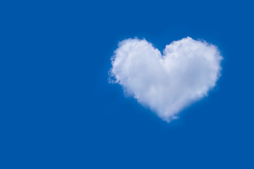 White soft and fluffy cloud with a heart shaped shown on fresh clear blue sky and sunshine day. Background for greeting card or love picture and Valentine's day or meteorology or inspiration concept.