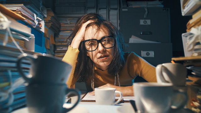 Stressed exhausted businesswoman working at night