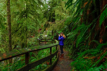 Woman takes pictures of beautiful trees while trekking around Hoh Rainforest.