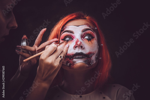 Talented makeup artist is creating special scary Halloween art on woman's face.