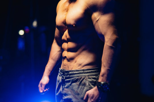 Attractive bodybuilder posing and showing off muscles on dark background. Half turn to the camera. Closeup. Blue light filter. Strong athlete with naked torso. Fitness concept.