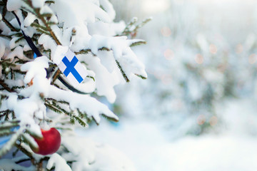 Christmas Finland. Xmas tree covered with snow, decorations and Finnish flag. Snowy forest background in winter. Christmas greeting card.