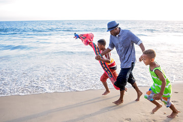 Father and his boys on the beach trying to fly a kite at sunset Fototapete