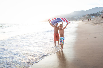 Patriotic fun at the beach boys running with the American flag
