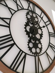 Large wall clock with Roman numerals, decorative gears and wooden bezel. The loft-style. Close-up