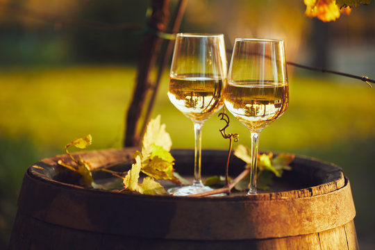 Two full glasses of white wine on wooden barrel in autumn