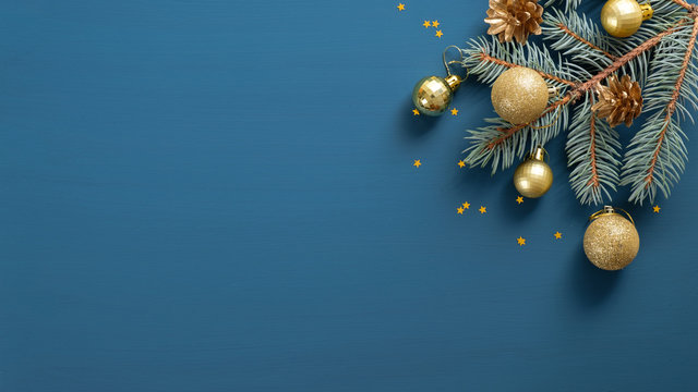 Christmas composition with green pine branch, golden decorations and balls, confetti on blue background with copy space. Top view, Flat lay. Xmas banner mockup, vintage postcard template