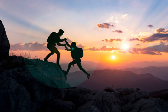 concept of male climber helping his girlfriend and moments of success together