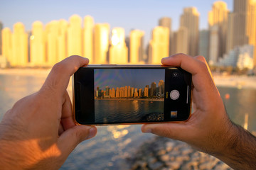JBR. Panoramic view of Jumeirah Beach Residence skyscrapers through mobile camera. View from the screen and taking picture of Dubai. Man taking photo of beach.