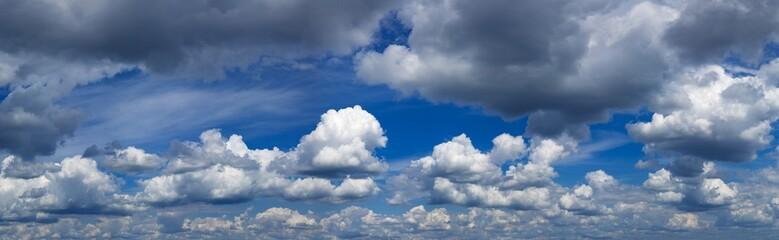 Blue sky with white and dark clouds. Panoramas photo.Stock photo