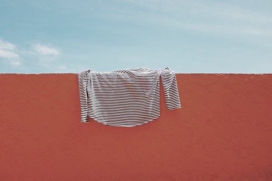T-shirt drying on wall against sky