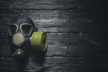 Gas mask on a black wooden background. Post apocalypse.