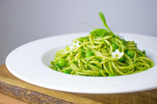 Food photography of spaghetti with a bright green ramp or wild garlic pesto