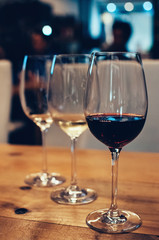 Close up image of three glasses with red and white wine, on wooden table, served for wine tasting event. Blurred background. Bar or restaurant interior, subdued light. Selective focus, film grain effe