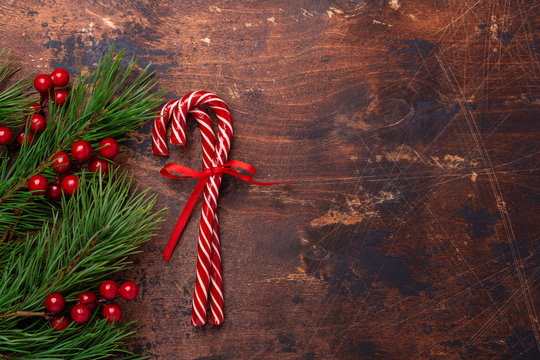 Candy canes with fir tree branches on wooden background. Christmas composition. New Year concept. Top view - Image