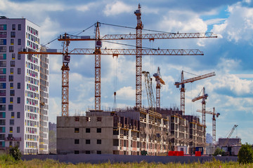 Construction. Building a new area. Cranes during operation. High-rise buildings. Designing high-rise buildings. New house is being built next to the already built one. Russia. Buildings in Moscow.