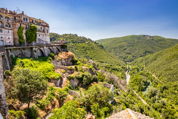 A characteristic glimpse of the ancient medieval village of Narni. Umbria, Terni, Italy. The blue sky on a summer day. The valley below with the green hills and the Nera river. Green trees.