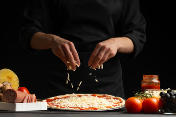 Zelfklevend Fotobehang Pizzeria Chef cooks pizza, sprinkled with mozzarella cheese, freezing in motion on the background with ingredients. Recipe book, menu, home cooking