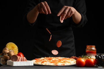 The chef cooks Italian pizza, sprinkled with slices of salami. Freeze in the air. Against the background of pizza ingredients. Black background, horizontal frame.