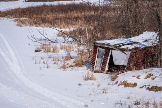 Abandoned boathouse on frozen river in winter
