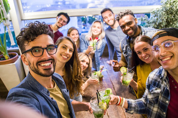 Happy friends taking a selfie at the restaurant drinking cocktails