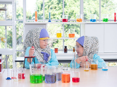 Two little Muslim cute girl study in science lab. Muslim  kid learning science and smiling.