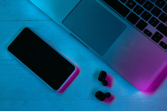 Top view of set of gadgets in purple neon light and blue background. Smartphone, laptop and wireless headphones on wooden table. Copyspace for your advertising. Tech, modern, gadgets.