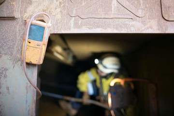 Unfocused, blurry picture of rope access miner working inside the confined space while yellow gas test detector atmosphere is hanging on the entry door frame, construction mine site Perth, Australia