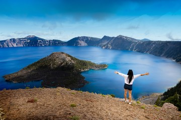 High angle shot of afemale admiring the view of Crater lake in the United States
