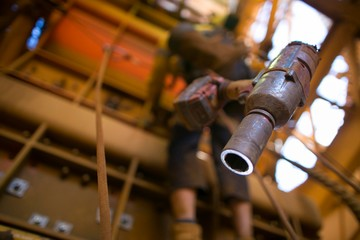 Picture of battery rattle gun clipping connecting into harness lop with blurry  rope access worker working at height at the background construction site, Perth, Australia