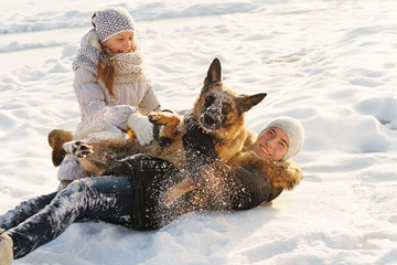 Joyful teens spend time together with lovely pet German Shepherd Dog on a walk in the winter park on a sunny day. Having fun playing in snow outdoors. Time for cheery. Happy family. Playful mood