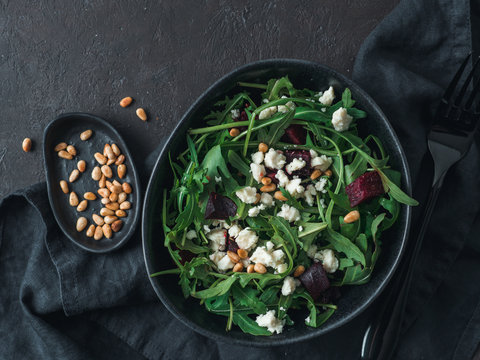Beetroot, aragula and soft cheese salad over black background. Top view or flat lay. Copy space for text. Idea and recipe for healthy vegetarian salad. Clean eating diet concept