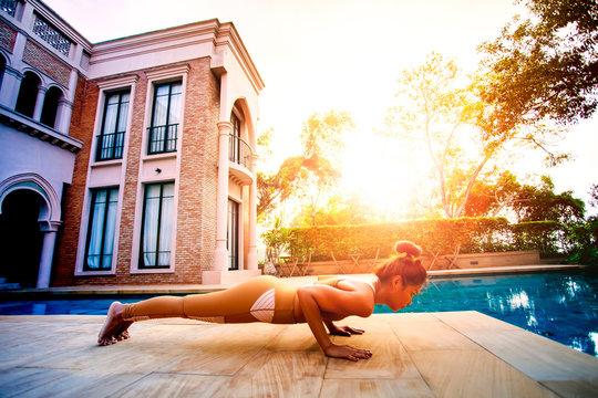 woman posting plank  yoga pose beside sport water pool