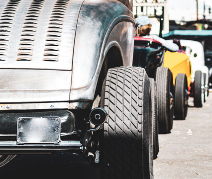 Rear end of a group of vintage roadsters at a racing event in denver colorado