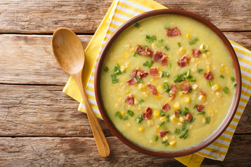Delicious vegetable corn chowder with bacon close-up in a bowl. Horizontal top view