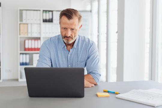 Worried senior businessman staring at his laptop