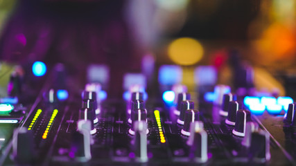 knop of sound control at DJ booth with colorful light bokeh, fun party concept